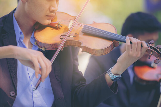 A musician man is practicing the violin playing with the melodiousness. Selected focus.