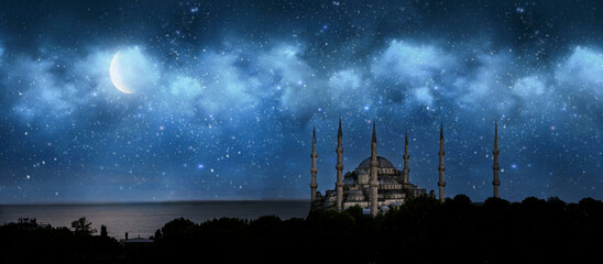 Fototapeta premium Istanbul, Turkey. Sultan Ahmet Camii named Blue Mosque. Front view of crescent shaped moon and mosque in front of night cloudy and starry sky. ramadan, the holy month of muslims. selective focus.