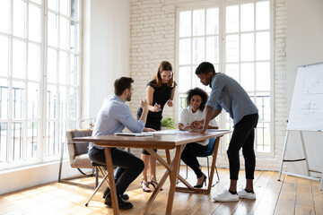 Full length motivated young diverse teammates gathering near table in modern office, working on corporate growth strategy development, analyzing paper marketing research report, discussing ideas.