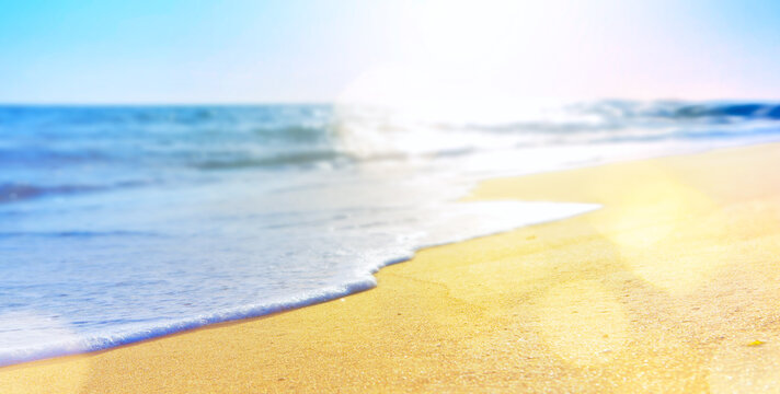 abstract summer vacation background of blurred beach sand and sea waves