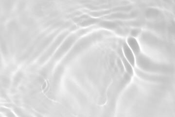 Closeup of desaturated transparent clear calm water surface texture with splashes and bubbles. Trendy abstract nature background. White-grey water waves in sunlight.