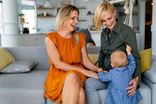 Happy lesbian female couple with her little child at home