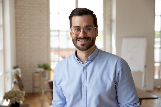 Portrait of smiling young 30s handsome bearded businessman in eyeglasses posing in modern workplace. Happy confident male entrepreneur worker employee looking at camera, professional career concept.