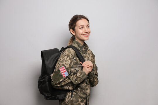 Female cadet with backpack on light grey background. Military education