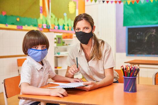 Tagesmutter und Kind mit Mundschutz in der Vorschule