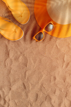 Summer beach holiday concept, flat lay top view with hat, sunglasses and flip flop slippers on sand