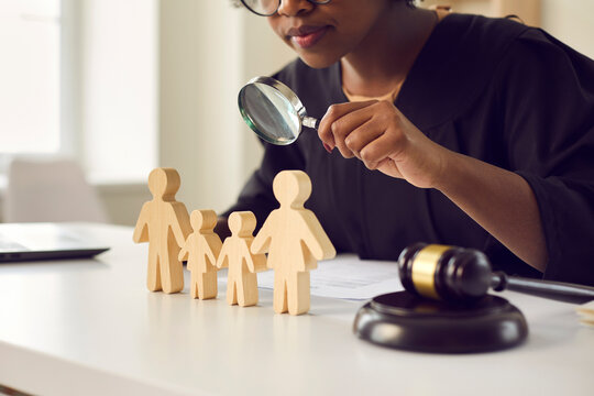 Black judge or lawyer looking in magnifying glass at little mom, dad children figures on desk. Family law court case investigation, divorce, joint custody of kid, parental rights deprivation concept