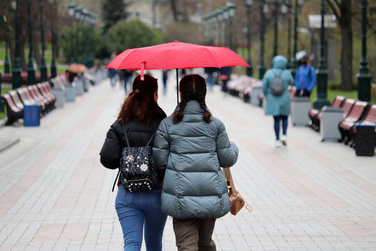 Rain in city, two girls with one red umbrella walk on a street on people background. Rainy weather, spring storm