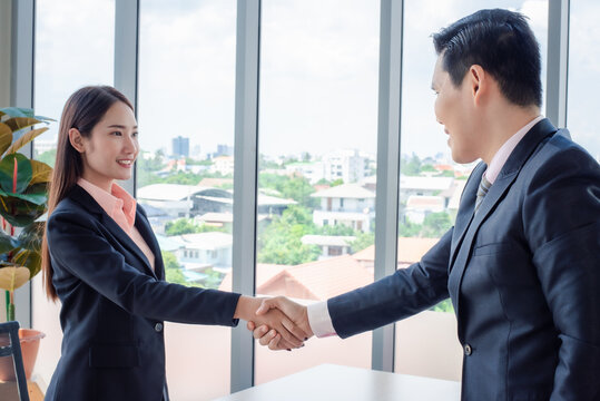 Businessman and woman shaking hands in office.