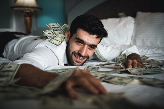 Successful businessman lay down in relaxing posture surrounding with dollar money.