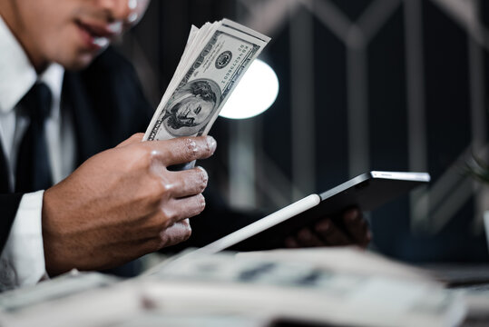 Selective focus. Close up of businessman hand offering batch of hundred dollar bills.Venality, bribe, corruption concept.