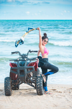 Asian young beautiful woman model in a bikini pose with ATV bike at the beach.summer vacation.