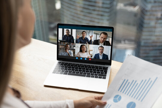 Female employee discuss paperwork with multiracial colleagues on video online call on laptop at home. Multiethnic diverse businesspeople talk speak on webcam zoom conference. Virtual event concept.