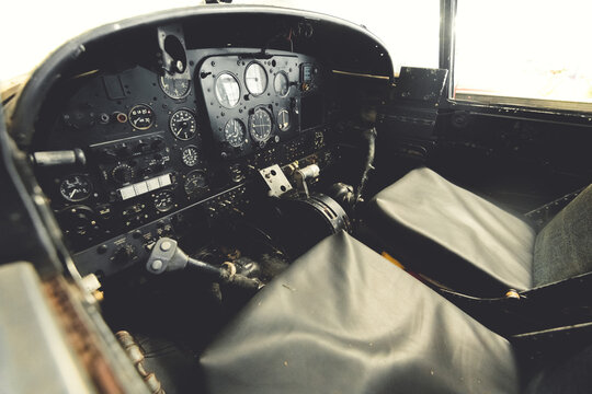 Close up of a planes cockpit showing instruments and panels from an old abandoned two seater plane