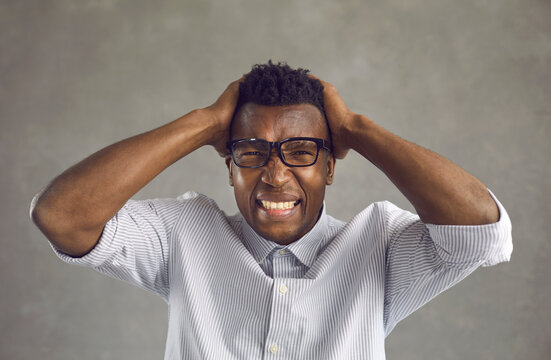 Crazy disturbed male corporate manager feeling angry. Stressed mad young black guy touches head pulling tearing hair out and grinding clenching teeth struggling to control overwhelming anger and fury