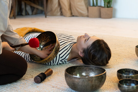 Alternative medicine and meditation: woman practice tibetan sound therapy and singing bowls massage at home. Recovery from music and zen vibrations. Himalaya yoga for mental health and stress relief