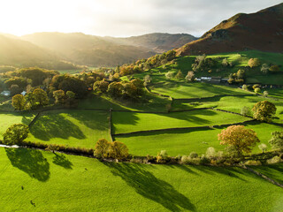 Aerial view of endless lush pastures and farmlands of England. Beautiful English countryside with emerald green fields and meadows.