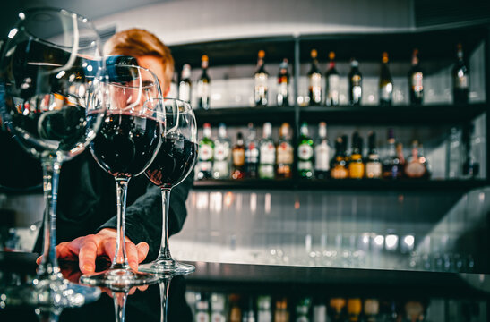 bartender pouring red wine into a glass in cafe or bar