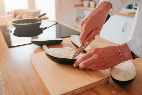 Unrecognizable cook at home making cuts in the eggplant to make it softer