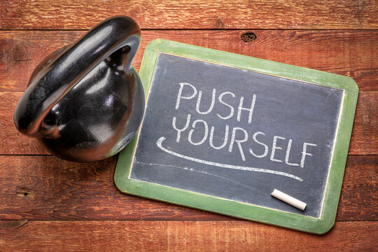 push yourself - white chalk text on a slate blackboard with a kettlebell, workout, training, exercise concept and personal development concept