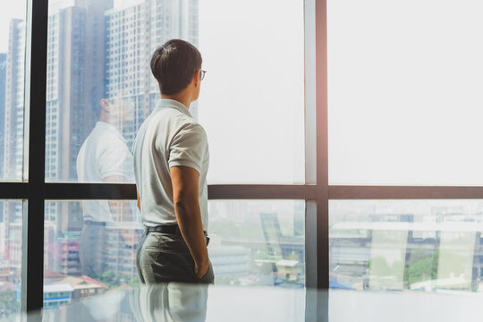Man standing with hands in pockets looking out of big window at city building.
