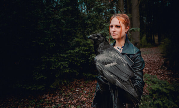 young woman or girl in the forest with a big black raven on his hand