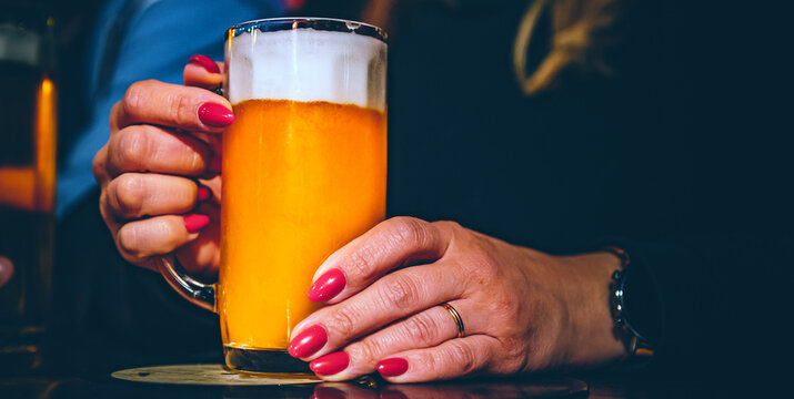 woman holds a glass of beer in his hand at the bar or pub