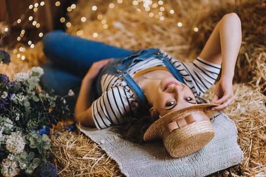 A beautiful pregnant girl in a straw hat lies in the hay in the countryside in a denim overalls. Photography, concept.