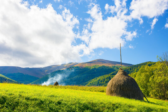 rural landscape with haystacks on the hill. fields and meadows in mountains. wonderful carpathian countryside scenery on a bright september day. clouds on the sky