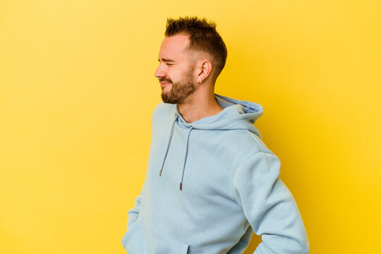 Young tattooed caucasian man isolated on yellow background suffering a back pain.