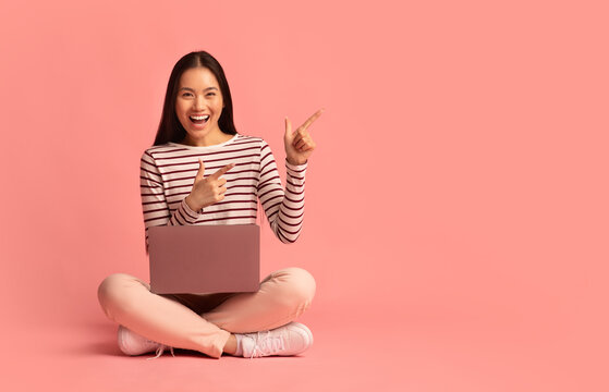 Asian woman sitting on floor with laptop and pointing at copy space
