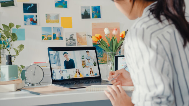 Young asia female employee listen leader on video call with diverse multiracial colleagues on online with laptop at home. Distance learning. Girl student learn online at house, Online meeting concept.