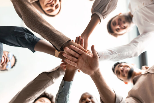 Diverse business people putting their hands together in cirle