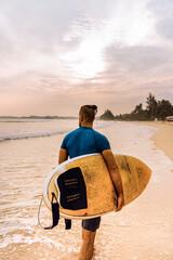 Surfer mężczyzna idący z deską po plaży na tle zachodu słońca.