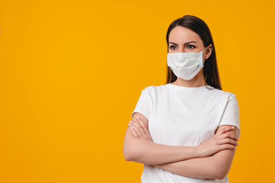 Young caucasian hispanic latin-american woman in protective face mask against Covid 19 coronavirus isolated over yellow background. Air pollution, allergy protection, pandemic concept