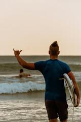 Fototapeta Surfer z deską surfingową na tle oceanu, mężczyzna uprawiający zdrowe sporty wodne.