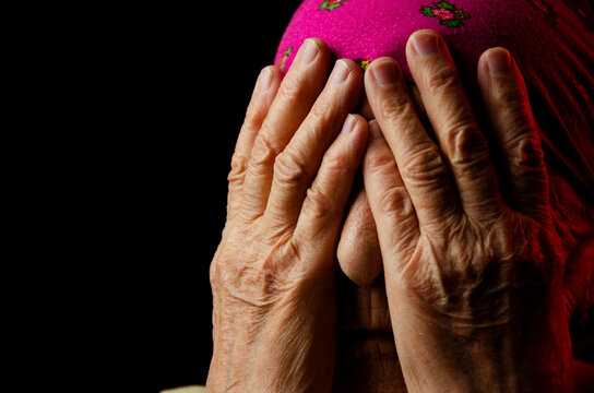 Old hands of a grandmother close up. Wrinkled hands close up. Old grandmother covered her face with her hands portrait photo. Seniors concept. Cover your face with your hands. Lonely old woman