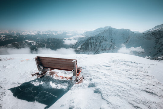 Wooden bench in the snow-capped Swiss Alps under a blue sky