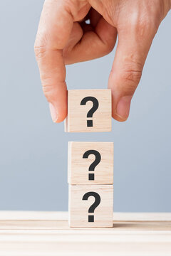 hand holding Questions Mark ( ? ) on wooden cube block on table background. FAQ( frequency asked questions), Answer, Q and A, Information, Communication and interrogation Concepts