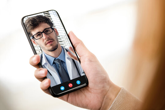 Patient making video call with doctor online via mobile phone, home medical consulation service and telemedical concepts
