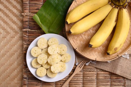Sliced banana fruit on white dish with fork ready to eating, Tropical fruit