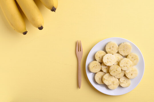 Sliced banana fruit with fork ready to eating on yellow background, Tropical fruit