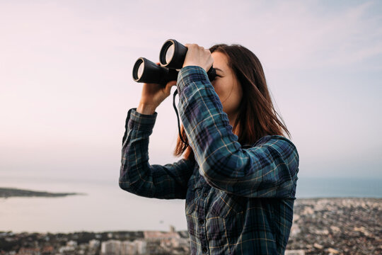 Portrait of a young female tourist looking through binoculars at sunset.