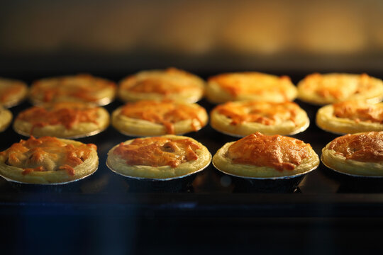 Mini pie from meat and mushrooms baking in oven, Pie and pastry wholesale bakery factory