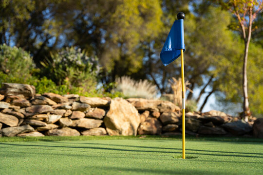 Blue golf flag on a miniature golf putting green
