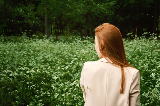 Mental Health Awareness Month, behavioral health care. Post COVID-19 pandemic mental health challenges. Red-haired young woman on green nature trees and flowers background
