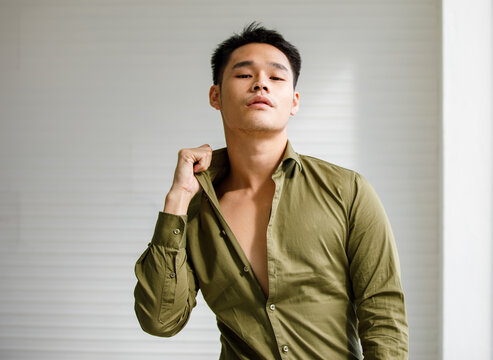 Young male in olive green shirt first four bottoms free. Posting little sexy feel sensuality. Studio shot in white room haft body.