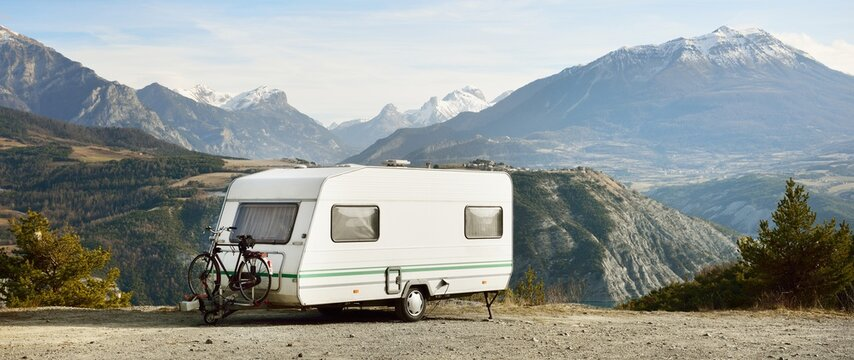 Caravan trailer, bicycle and car parked on a mountaintop with a view on French Alps near lake Lac de Serre-Poncon. Transportation, RV, motorhome, road trip, camping, tourism, recreation, lifestyle