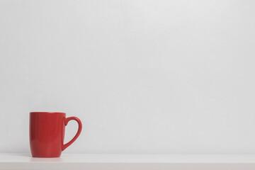 A red coffee mug on white wall.