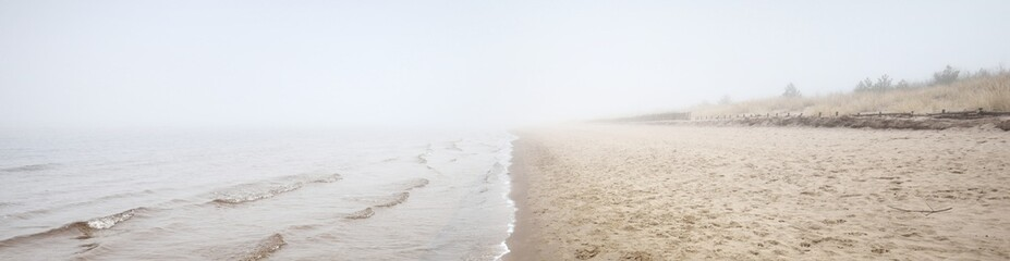 Fototapeta Sandy shore of the Baltic sea in a thick white morning fog. Early spring in Latvia. Idyllic rural scene. Nordic walking, recreation, eco tourism, environmental conservation concepts